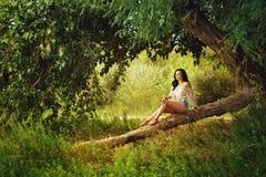 Boho dziewczyny obsiadanie na spadać drzewie w lesie Obraz Stock