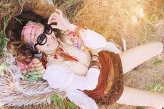 Boho dziewczyny portreta stylowy szczęśliwy uśmiechnięty lying on the beach na futerku i sianie Fotografia Stock