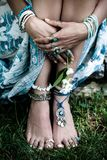 Boho fashion details woman hands and bare feet on grass with lot. Of bohemian style jewrly rings bracelets summer day royalty free stock images