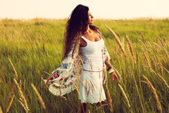 Boho fashion. Woman wearing boho style clothes in the field , hot summer day, retro colors stock photography