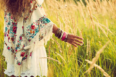 Boho fashion. Woman wearing boho style clothes touching grass, hand with lot of braceletes, summer day in the field, retro colors stock image