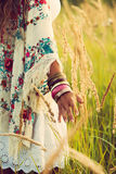 Boho fashion. Woman wearing boho style clothes touching grass, hand with lot of braceletes, summer day in the field, retro colors Royalty Free Stock Images