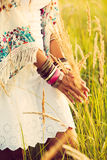Boho fashion. Woman wearing boho style clothes touching grass, hand with lot of braceletes, summer day in the field, retro colors Stock Photo