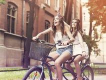 Boho flickor som rider på cykeln Royaltyfri Fotografi