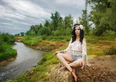 Boho Girl contemplates on bank of river. Royalty Free Stock Image