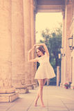 Boho Girl dancing outdoors. Carefree young girl in a white dress on the street. Trendy lifestyle portrait. Girl dancing on the background of columns. Sunset royalty free stock images
