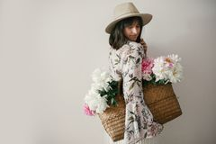 Boho girl in hat holding pink and white peonies in rustic basket. Stylish hipster woman in bohemian floral dress posing with royalty free stock photos