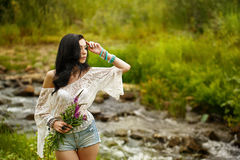 Boho Girl holding bouquet of wildflowers. Royalty Free Stock Photos