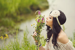 Boho Girl sniffing bouquet of wildflowers. Stock Images