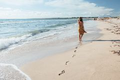 Boho girl walking on the beach Royalty Free Stock Image