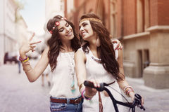Boho girls with bike. Boho girls walking alley of city royalty free stock photos
