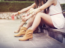 Boho girls relaxing. Part of hippie women sitting on curb stock images