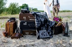 Boho wedding couple standing near vintage suitcases, near old retro cameras, camera cases and old lamp Royalty Free Stock Images