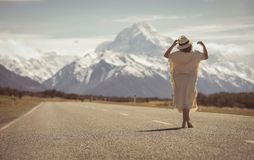 A boho hippy lady in white dress with hat stands on road with ao stock photo