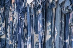 Boho hippy shades of blue tie died dresses hanging on a rack stock photography