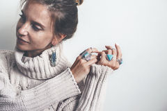 Boho jewelry and woolen sweater on model. Boho jewelry on model: ethnic stone rings and earrings. Beautiful woman wearing warm woolen sweater and fashion Royalty Free Stock Image