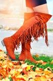 Boho-Mädchen, das in kniehohe Fransenstiefel am Herbsttag geht stockfotos