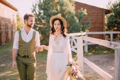 Boho-stil nygifta personer går på ranchen, sommardag royaltyfria foton