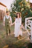 Boho-stil nygifta personer går på ranchen, sommardag arkivbilder