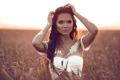 Boho stilstående av den bohemiska flickan med vit konst som poserar över vetefält på solnedgången Utomhus foto Lugnbegrepp royaltyfri bild