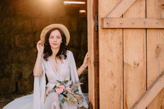 Boho style bride sitting near hayloft on ranch royalty free stock photography