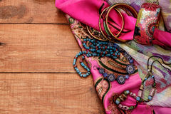 Boho style and hippie fabrics, bracelets, necklaces. Brown wooden table with ornaments in the style hippie Stock Photos