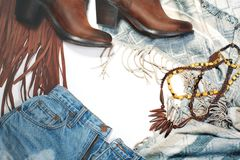 Boho Style. Leather Boots, Denim and Bag with Fringe on White Background. Overhead View Casual Day Outfits. Trendy Look. Boho Style. Leather Boots, Wooden stock photography