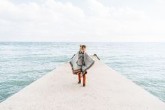 Boho style woman on pier. Beautiful boho style woman walking on sea pier royalty free stock photo