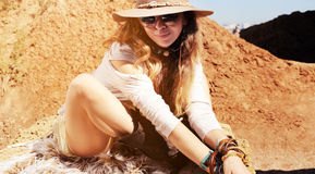 Boho style woman portrait sitting on fur, fashion hat, sunglasses and wristbands. Sunny outdoor, African safari travel concept Royalty Free Stock Photography