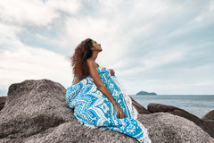 Beautiful young covered with blanket woman on the beach. Boho styled fashion model look in the sky while sitting on the rock Stock Images