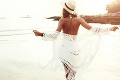 Boho styled model on the beach. Beautiful boho styled model wearing white crochet swimsuit posing on the beach in sunlight stock images