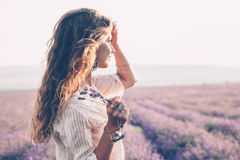 Boho styled model in lavender field. Beautiful model walking in spring or summer lavender field in sunrise backlit. Boho style clothing and jewelry royalty free stock images