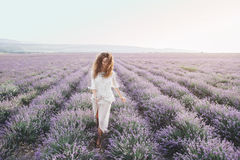 Boho styled model in lavender field. Beautiful model walking in spring or summer lavender field in sunrise backlit. Boho style clothing and jewelry Stock Photos