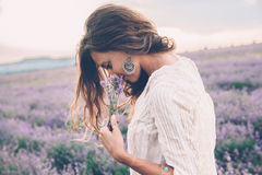 Boho styled model in lavender field. Beautiful model walking in spring or summer lavender field in sunrise backlit. Boho style clothing and jewelry stock images