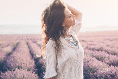 Boho styled model in lavender field. Beautiful model walking in spring or summer lavender field in sunrise backlit. Boho style clothing and jewelry royalty free stock image