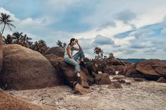 Boho styled young fashion model sitting on a stone at the beach. Attractive young fashion model outdoors on tropical island Stock Images
