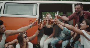 Boho stylish group of friends drinking beer and cheers at the picnic party , sitting behind the retro van.  stock video footage