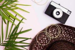 Boho stylu egzamin próbny up: palma liście, rocznik kamera, złoci bangles i plażowy kapelusz na, kolorowych menchiach i purpury t Zdjęcie Stock