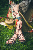 Boho summer fashion. Woman legs  on grass in strap flat sandals and boho style silky  dress  with lot of bracelets on hands Royalty Free Stock Photography