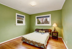 Boho themed bedroom with green walls, and hardwood floor. Royalty Free Stock Images