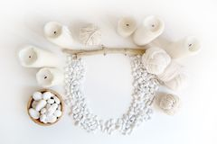 Boho white mockup with candles, cotton yarn and white sea pebble on the desk. Top view flat lay. Space for your text royalty free stock photography