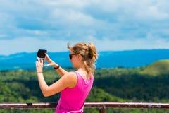 BOHOL, ФИЛИППИНЫ - 23-ЬЕ ФЕВРАЛЯ 2018: Девушка с камерой на предпосылке холмов шоколада фокуса съемка outdoors селективная стоковое фото rf