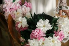 Bohomeisje die roze en witte pioenen in handen houden bij rustieke houten stoel Modieuze hipstervrouw in Boheemse kleding die pio stock foto
