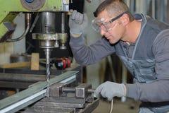 Bohrendes Metall der Arbeitskraft mit großem bohren herein Werkstatt stockfotografie