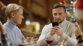 Bohrendes Weihnachtsessen mit Smartphones, Abschluss oben auf Paaren stock video footage