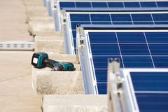 Bohrer durch den Sonnenkollektorflachdachbau Stockfotos