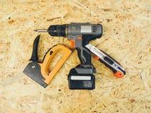 Bohrgerät, Baumesser und Bauhefter auf einem hölzernen Hintergrund stockbilder