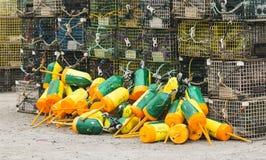 Boia amarelas e verdes com as armadilhas da lagosta na terra Foto de Stock