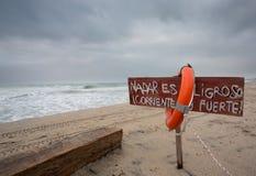 Boia e sinal de vida perigosos para nadar Imagens de Stock