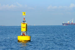 Boia navegacional amarela de flutuação no mar azul foto de stock